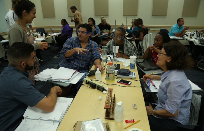 Melissa Maestu '06 former institute participant was a facilitator at this year's physical sciences institute. Here, she coaches a group of teachers who are also FIU alumni through an experiment.